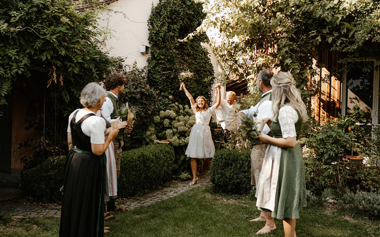 Die Braut und der Bäutigam kommen voller Freude in den Garten und werden von den Gästen freudig empfangen.