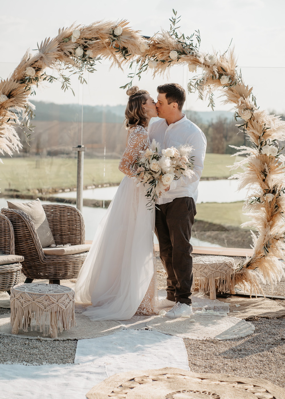 Das Hochzeitspaar, eine Frau mit langem weißen Spitzenkleid und ein Mann mit dunkler Hose und weißem Hemd stehen im Außenbereich der Location und küssen sich unter dem Traubogen bei der Pampasgras Hochzeit.
