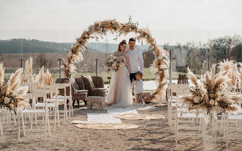 Das Hochzeitspaar steht zusammen mit dem ca. dreijährigen Sohn unter dem Traubogen aus Pampasgras im Außenbereich der Hochzeitslocation. Die weißen Stühle sind so angeordnet, dass die Blicke der Gäste auf das Paar gerichtet sein werden.
