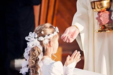 Mädchen kniet vor dem Priester und erhält ihre Erstkommunion durch die Vergabe des Leib Christi