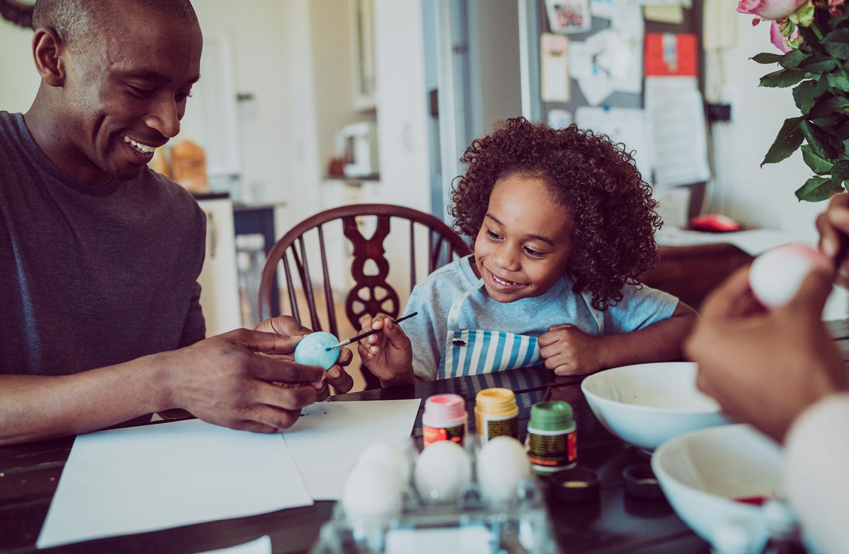 Familie bemalt am Tisch gemeinsam Ostereier in bunten Farben zu Ostern.