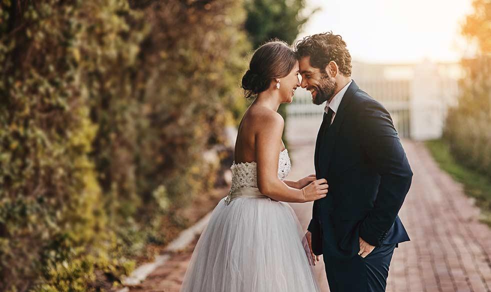 Verliebtes Brautpaar lacht sich an und ist glücklich.