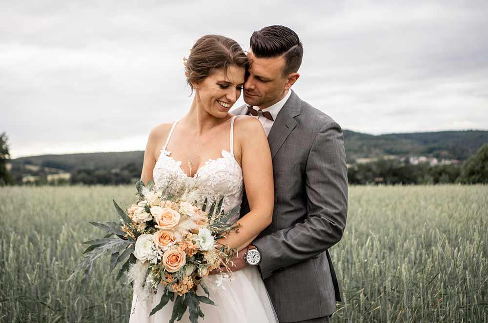 Verliebtes Brautpaar im Feld lächelt sich an.