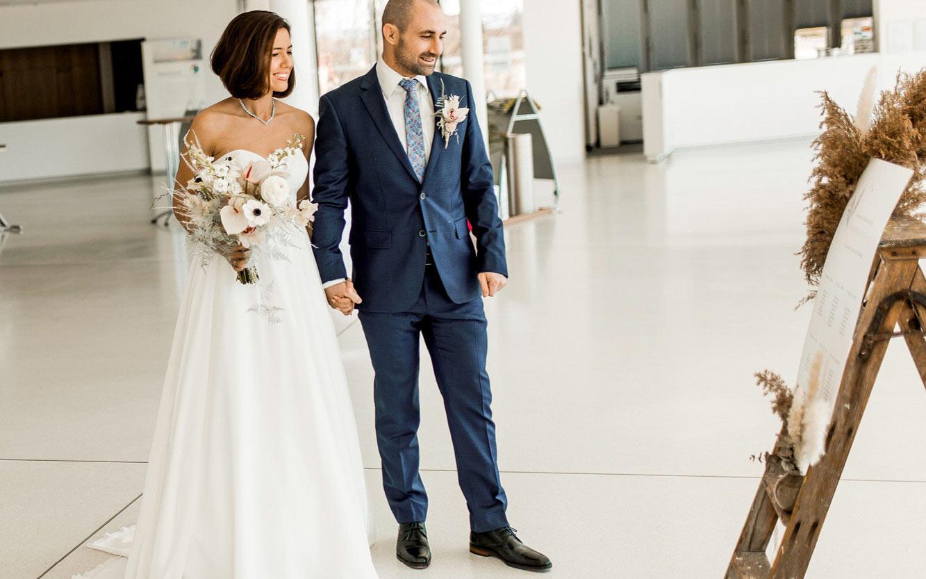 Braut und Bräutigam stehen vorm Sitzplan