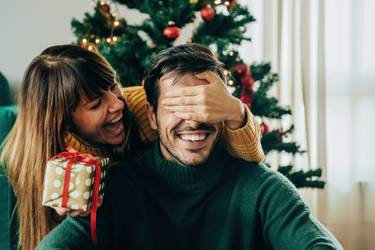 Junge Frau überrascht Mann mit Weihnachtsgeschenk