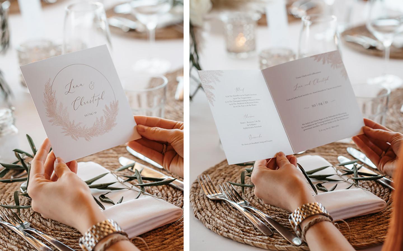 Die Hochzeitseinladung ist weiß und wird mit einem goldenen Bogen und Pampaswedeln geschmückt, die handgezeichnet sind. Die Namen des Paares stehen in dem Bogen. Man sieht die Karte zugeklappt und aufgeklappt.