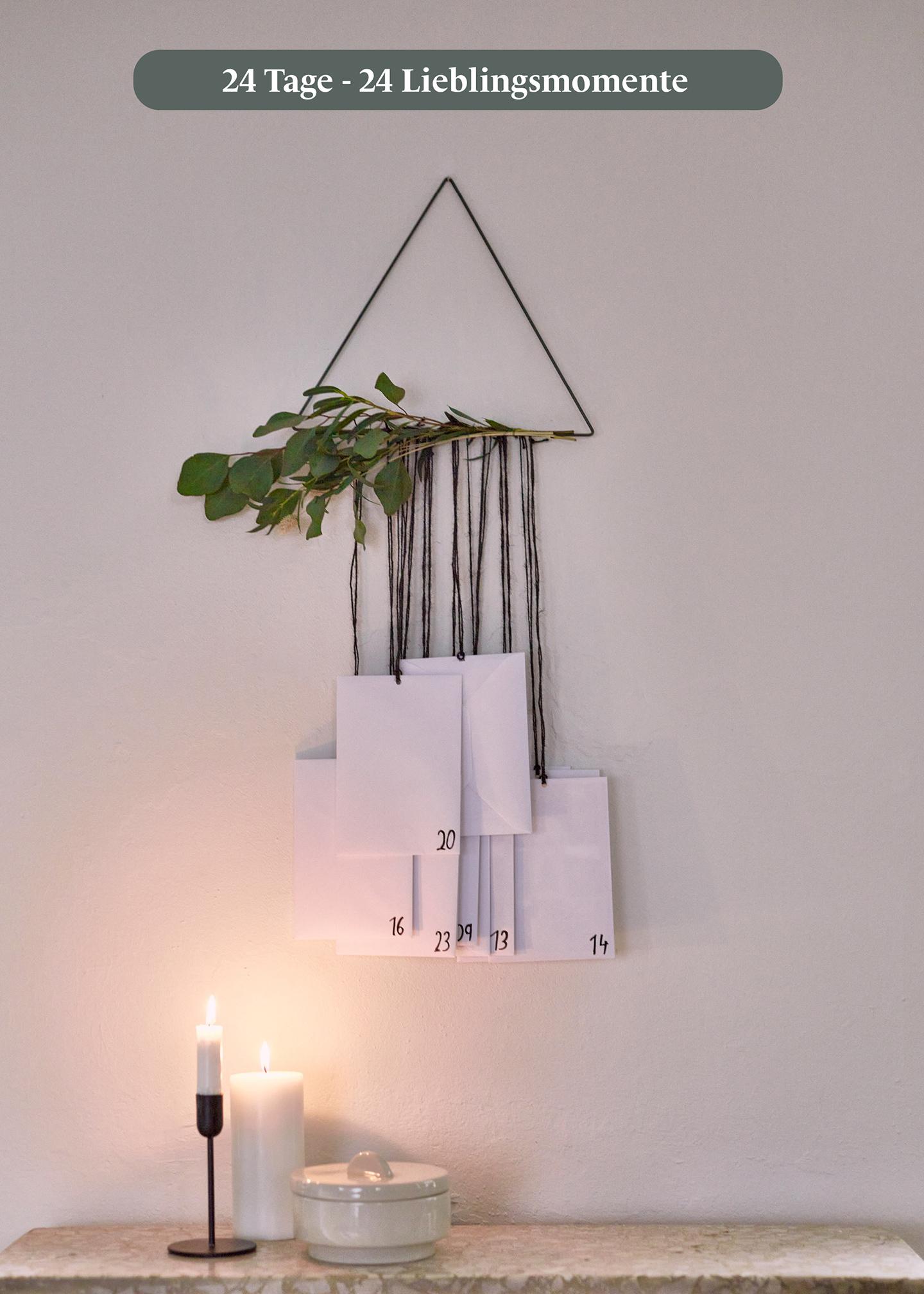 Adventskalender selber basteln: Dreieck mit Zweigen hängt an der Wand und Umschläge für jeden Tag enthalten ein Foto.