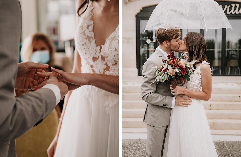 Brautpaar steckt sich im Standesamt die Ringe an und küsst sich unter einem Regenschirm.
