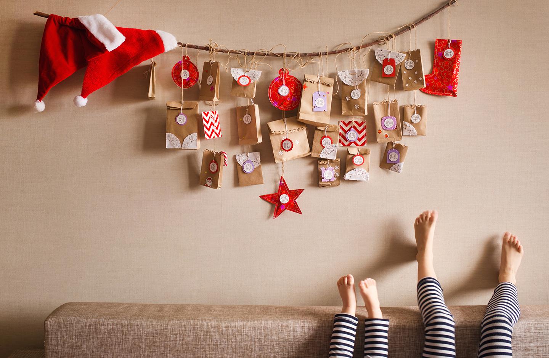Adventskalender aus Kraftpapiertüten hängt an der Wand und ist mit Weihnachtsmützen dekoriert.