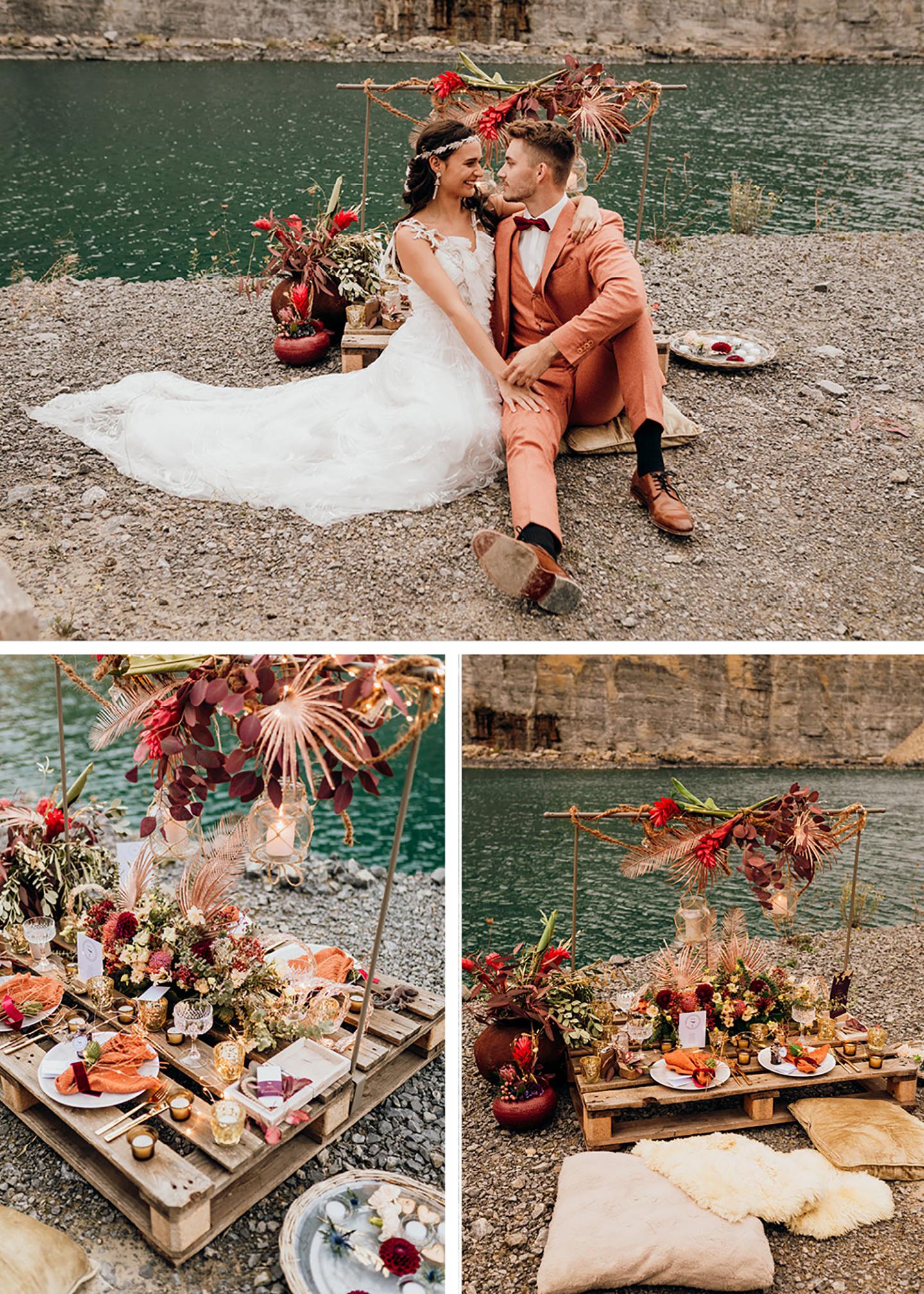 Die Hochzeitstafel und Blumendeko der Hochzeit sowie das auf Kissen sitzende Brautpaar vor dem Wasser im Steinbruch