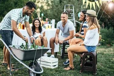Fünf Freunde sitzen im Garten und feiern glücklich eine Gartenparty.