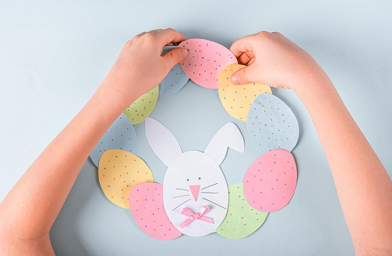 Basteln zu Ostern: Bunte Ostereier werden aus Papier ausgeschnitten und als Kranz zusammen geklebt.