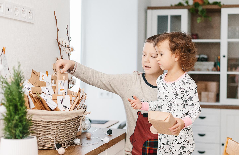Zwei kleine Kinder öffnen aufgeregt das erste Paket des Adventskalender.