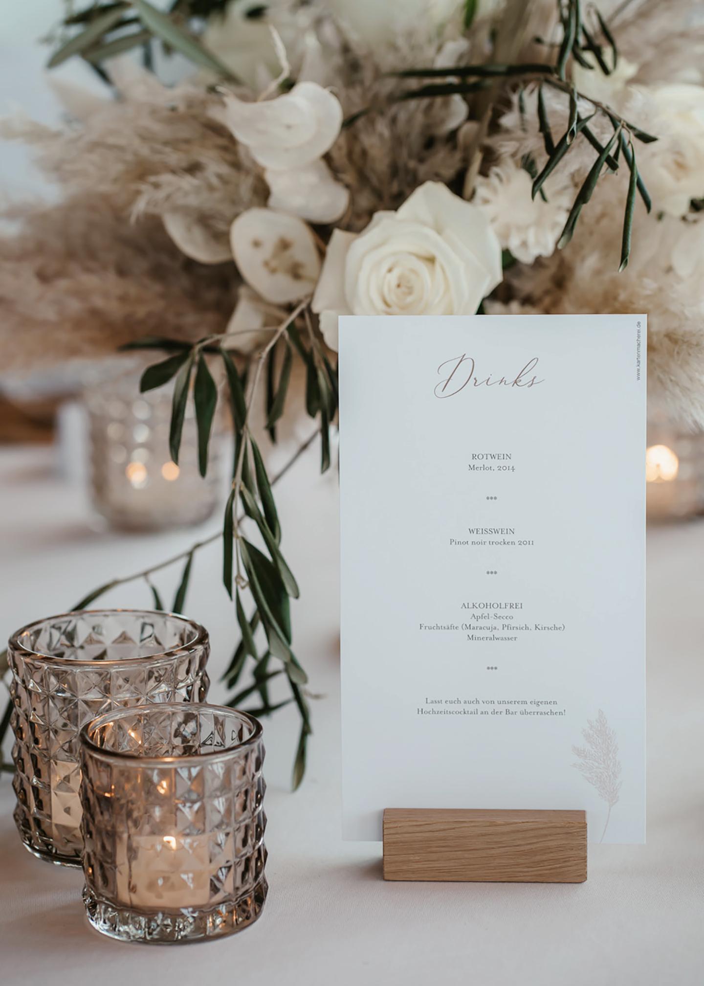 Die Menükarte ist von der Seite zu sehen, auf der die Getränke untereinander aufgelistet werden. Die Papeterie gleicht der Hochzeiteinladung in weiß mit gezeichneten Pampaswedeln und steht auf dem Hochzeitstisch.
