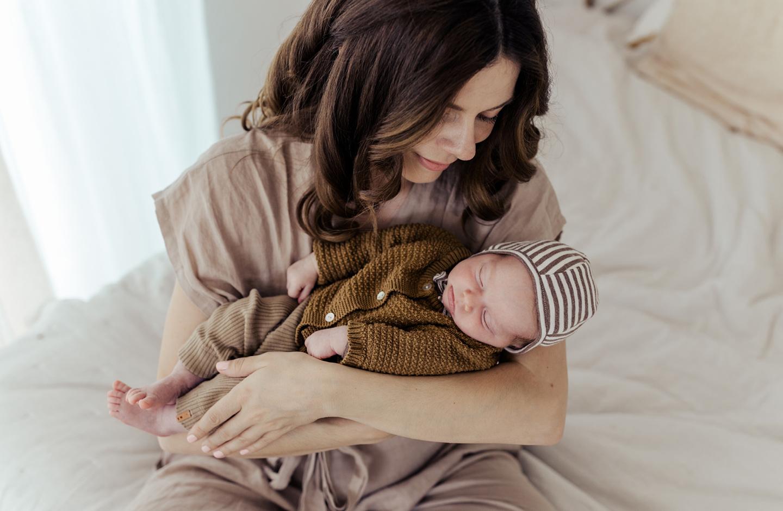 """Mama hält ihr schlafendes Baby mit nordischem Mädchennamen """"Lenja"""" auf dem Arm."""