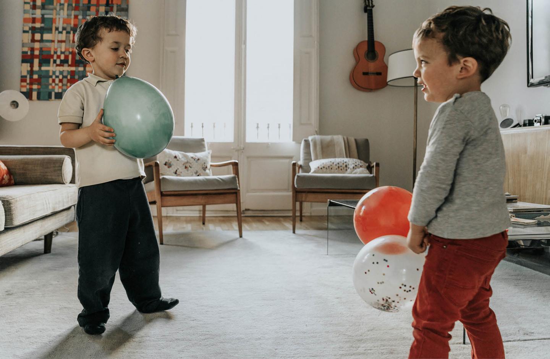 Zwei kleine Jungs spielen im Wohnzimmer mit Luftballons