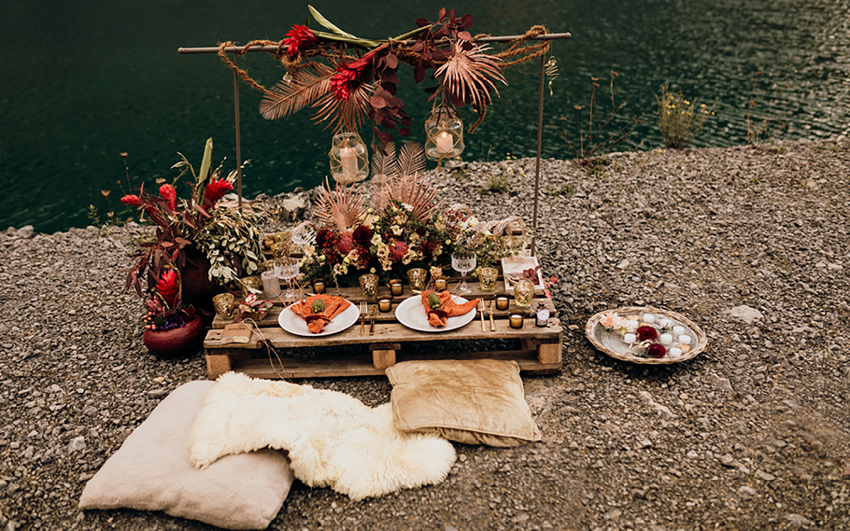 Tischdeko Hochzeit: Boho-Look im Steinbruch: Der Hochzeitstisch aus einer Holzpalette ist liebevoll geschmückt in warmen, leuchtenden Farben. Rot, Orange und Beige wirken wunderbar zusammen kombiniert.
