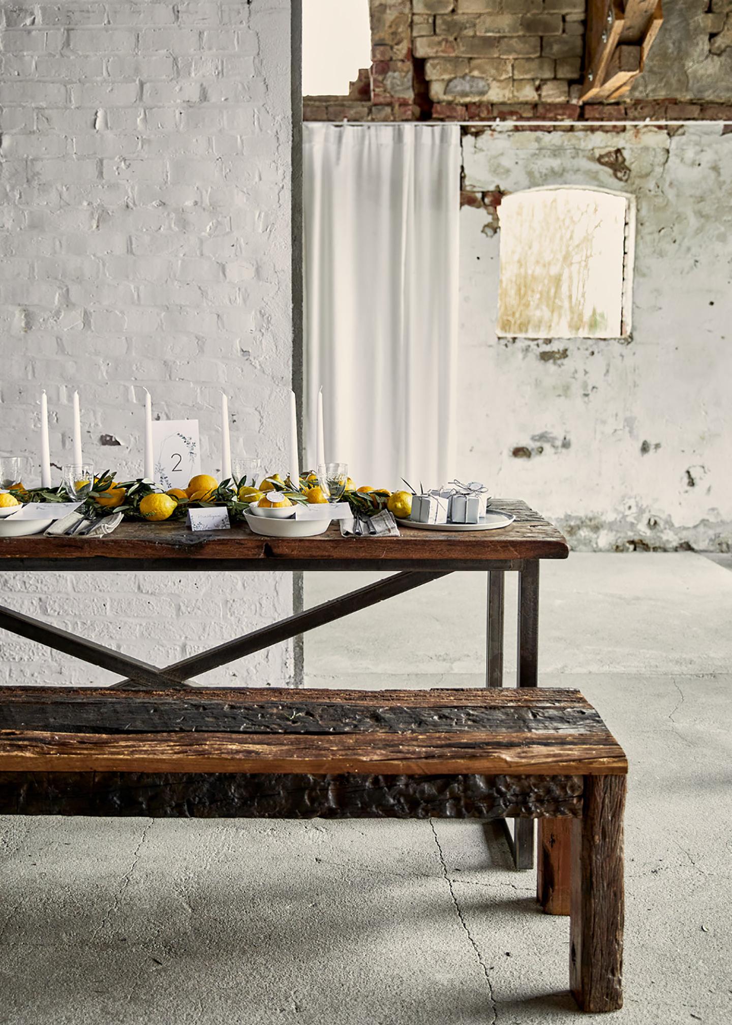 Rustikale Holzbank mit dazu passendem Tisch, dekoriert im schlichten Look mit Zitronen als Haupt-Dekoelement. Die Location ist im Shabby-Look gehalten.