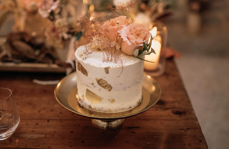 Einstöckige Hochzeitstorte mit gold Akzenten und rosé farbiger Blumendekoration