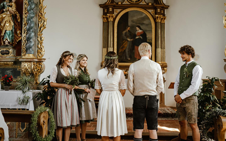 Die Trauzeugen und das Hochzeitspaar stehen vorne in der Kirche. Die Trauung steht kurz bevor, sie sind von hinten vom Eingang der Kirche heraus zu sehen.