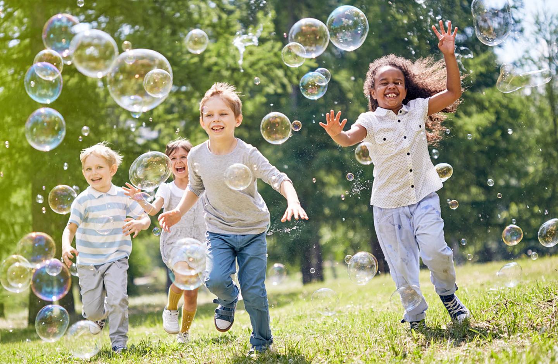 Kinder jagen im Garten Seifenblasen hinterher und haben sichtlich Spaß daran.