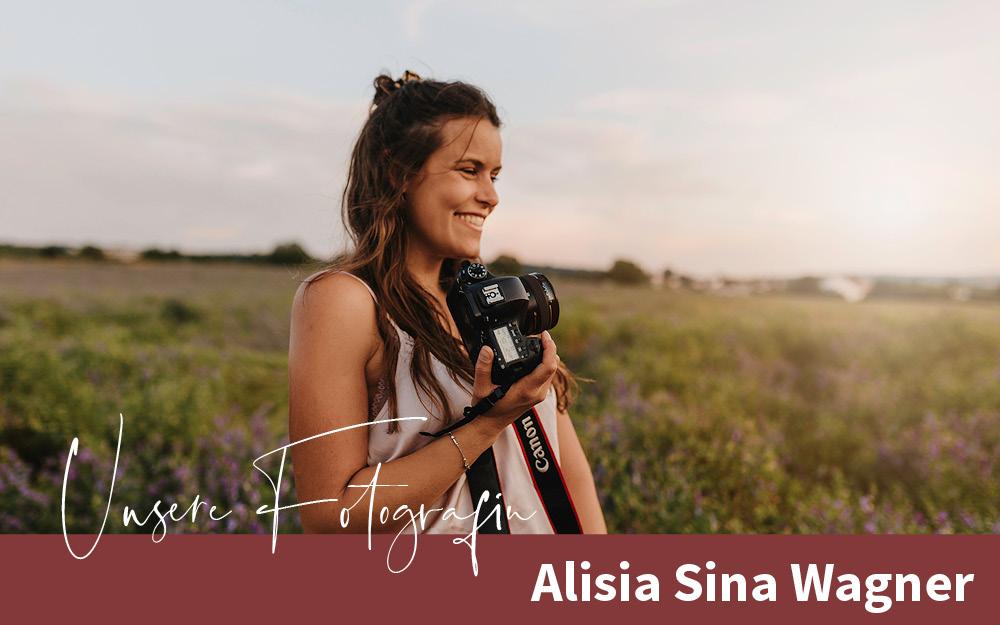 Fotografin Alisia Sina Wagner auf einem Feld, lachend mit Kamera