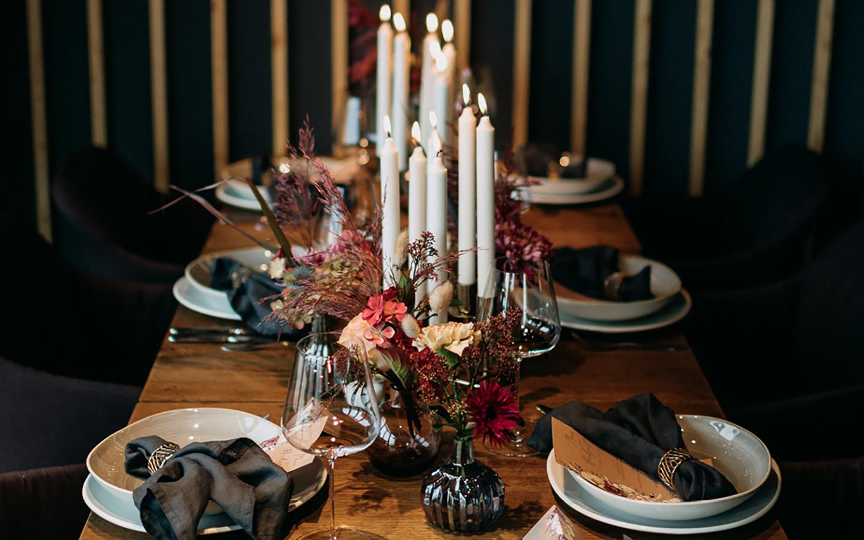Ein stilvoll angerichteter Hochzeitstisch in klassisch, romantischem Stil. Die Farben sind in dunkleren Tönen gehalten und die Blumen rot, pink und hellbeige.