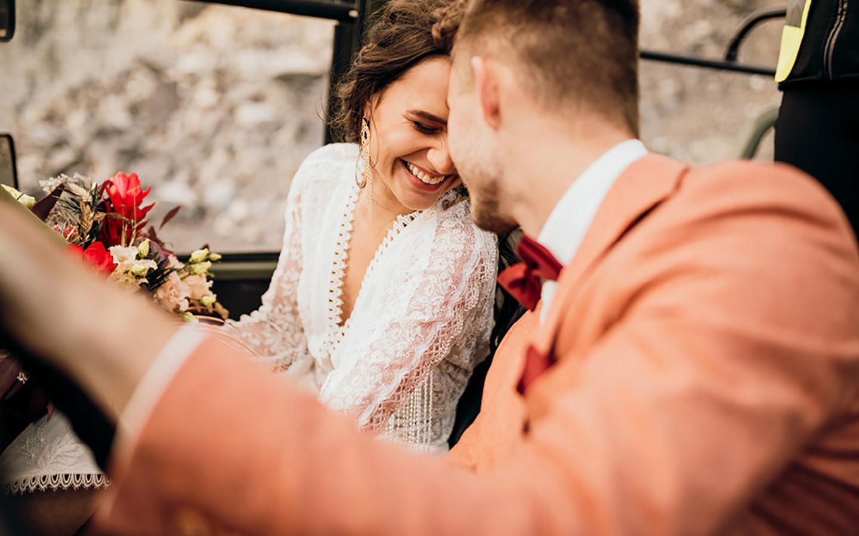 Verliebtes Brautpaar sitzt lachend nebeneinander im Geländewagen.