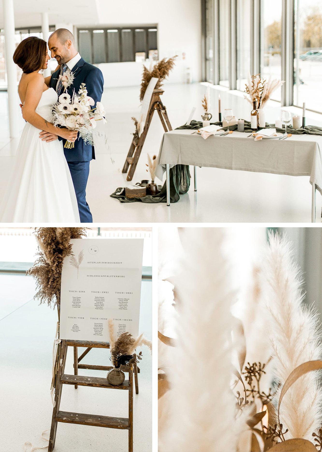 Braut und Bräutigam stehen vorm Hochzeitstisch, Sitzplan mit Pampas Dekoration ist zu sehen.