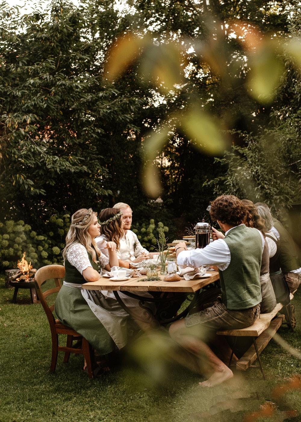 Eine gemütliche Runde aus Gästen und Hochzeitspaar sitzt im Garten und freut sich über den Kuchen.