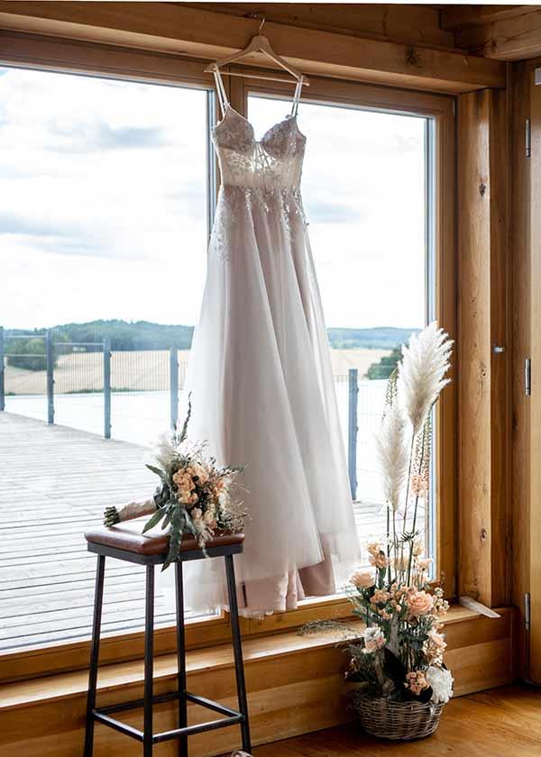 Brautkleid mit Transparenz hängt am Fenster.