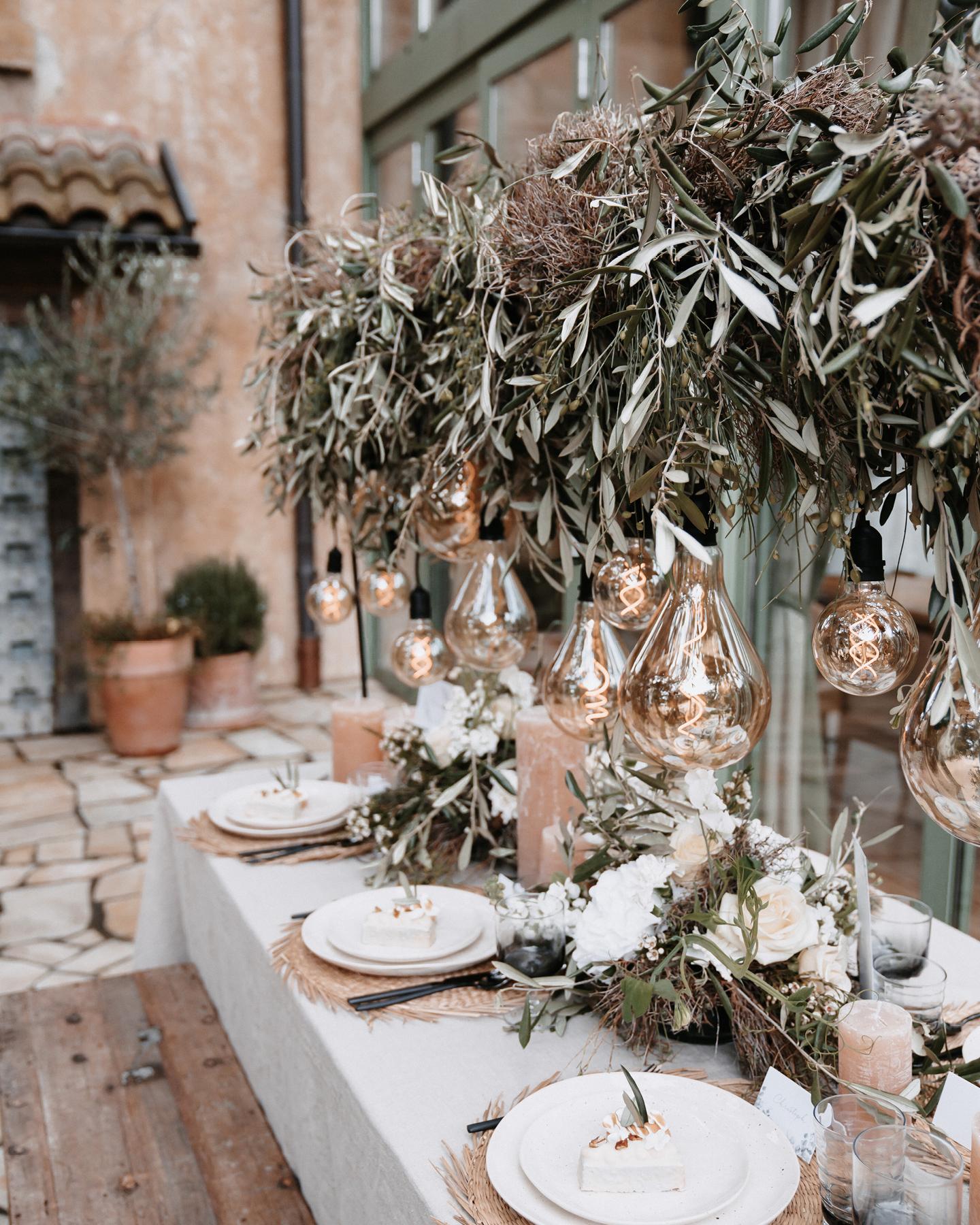 Die Hochzeitstafel ist dekoriert mit Euklayptuszweigen, weißen Blüten und einer Lichterkette im Boho Stil.
