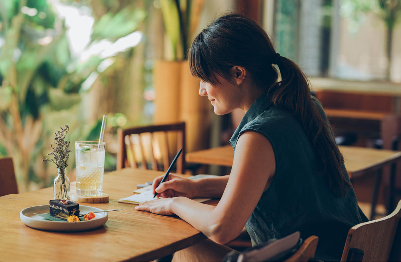 Eine Frau sitzt am Tisch und schreibt einen Brief.