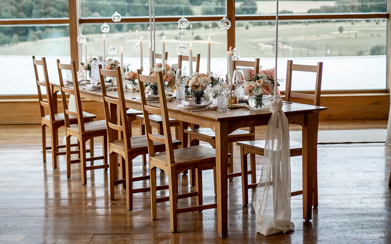 Der hellbraune Hochzeitstisch wurde komplett hergerichtet und mit pastelligen Deko-Elementen geschmückt.