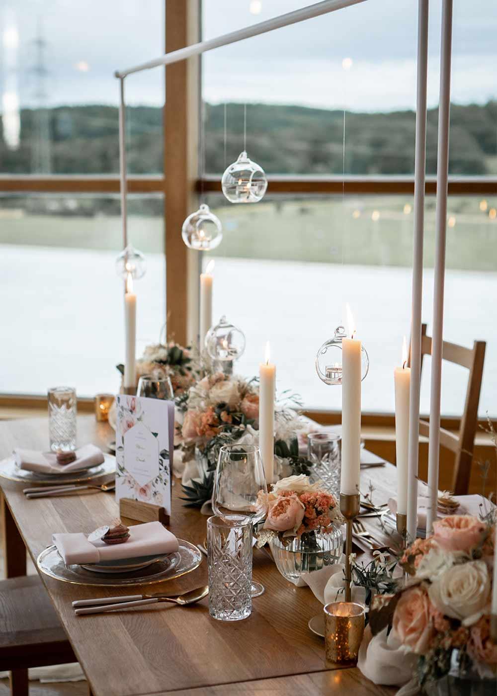 Hochzeitstafel aus Holz dekoriert mit Kerzen in Weiß und sanften Blumen.