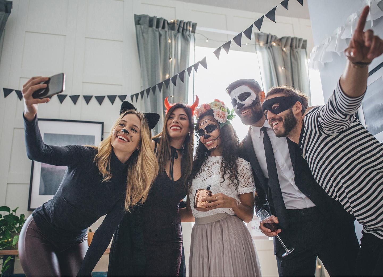 Freunde feiern Halloween in gruseligen Kostümen
