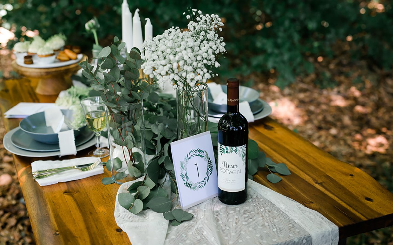 Tischdeko Hochzeit: Ein Hochzeitstisch im Greenery Look: Eukalyptus und Schleierkraut auf der rustikalen Tafel geben ein harmonisches Bild.