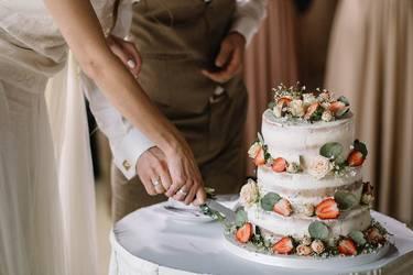 Brautpaar schneidet die drei stöckige Hochzeitstorte an, die mit Blumen und frischen Erdbeeren verziert ist
