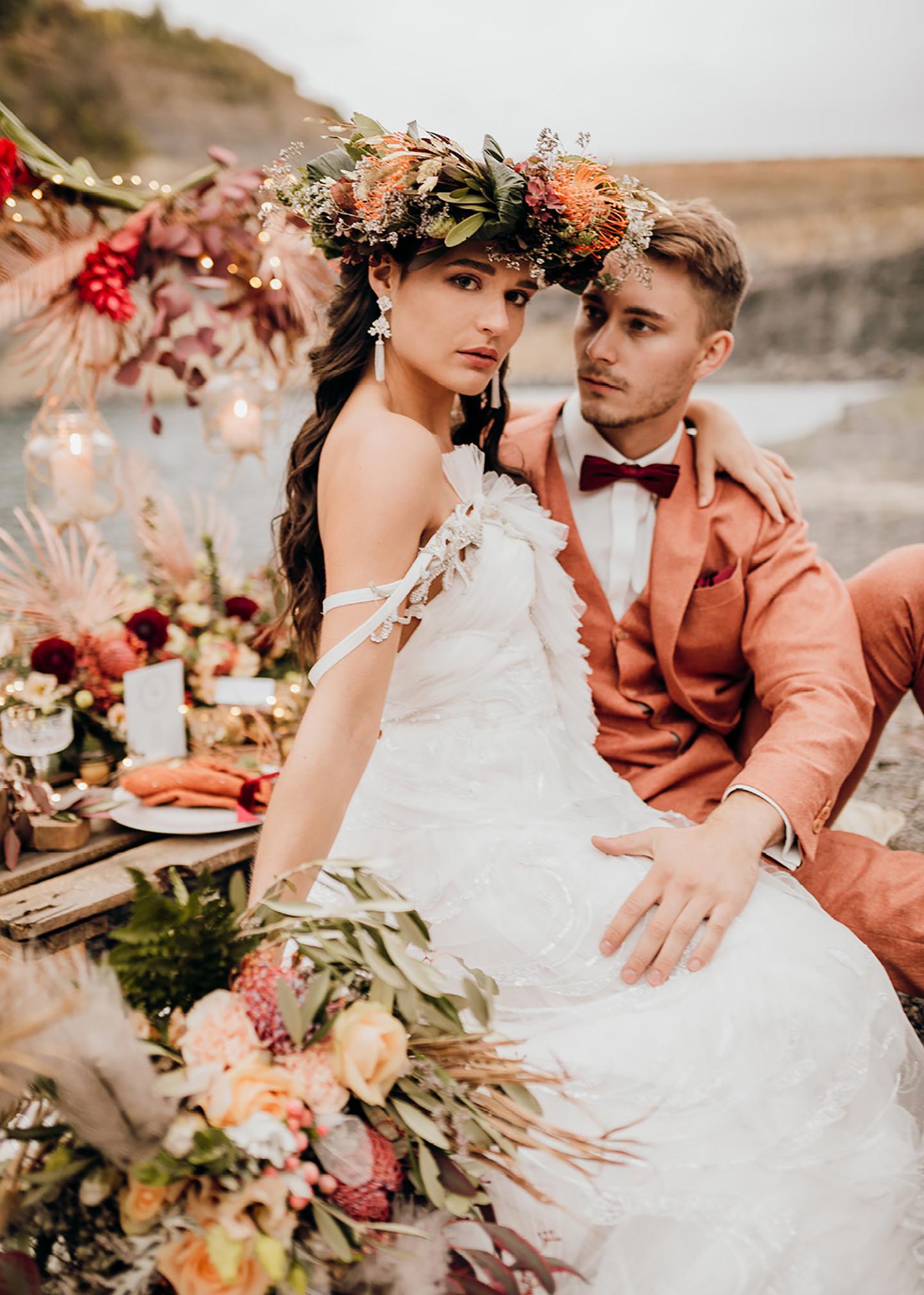 Das Brautpaar sitzt auf der selbstgemachten Hochzeitstafel, die in Rot- und Orangetönen geschmückt ist. Die Braut hat eine Blumenkrone auf ihrem Kopf.