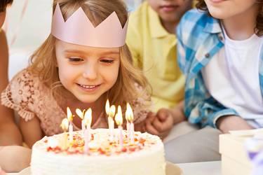 Geburtstagskind mit Krone auf auf dem Kopf sitzt mit seinen Geburtstagsgästen am Tisch und pustet die Kerzen auf der Torte aus