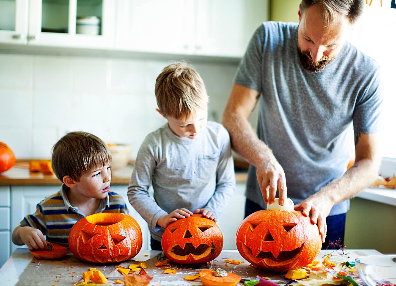 Papa und Söhne schnitzen Kürbisse für Halloween Party