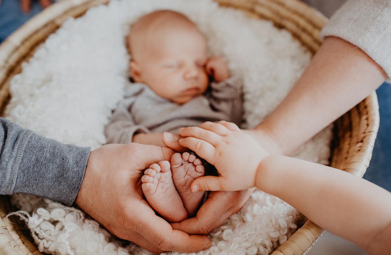 Mama, Papa und Schwester halten Hände um die Füße des Neugeborenen mit einem nordischen Mädchennamen.